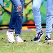 Two people's legs in jeans wearing sneakers