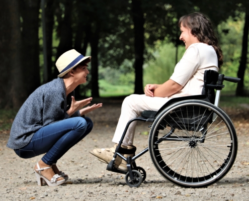 one young person in a wheelchair having a chat to another young person outdoors
