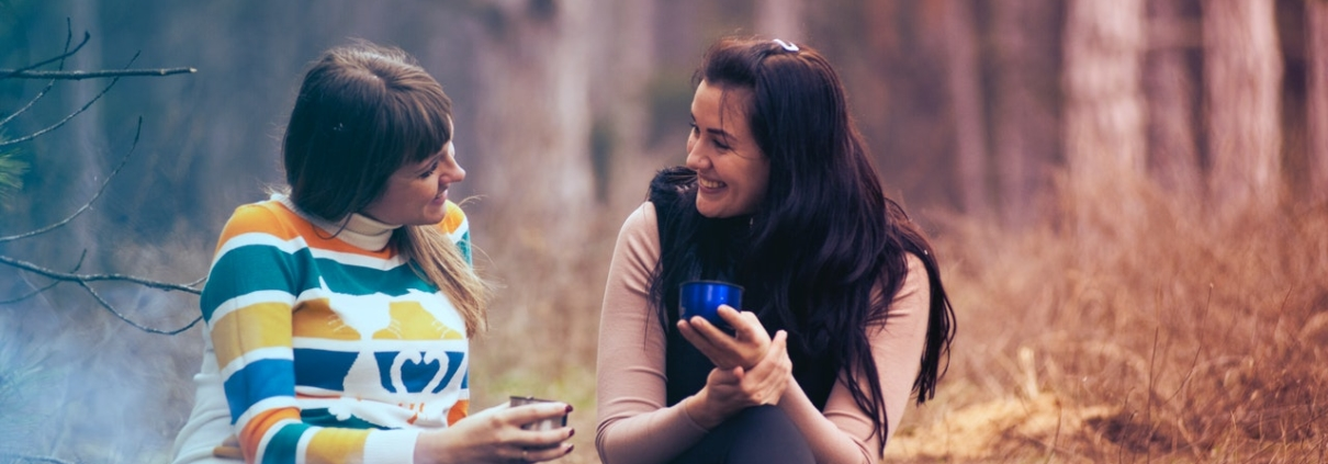 Two women sitting in front of a campfire and talking with each other