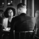 Woman sitting in a cafe facing a man with angry look whose back is to camera.
