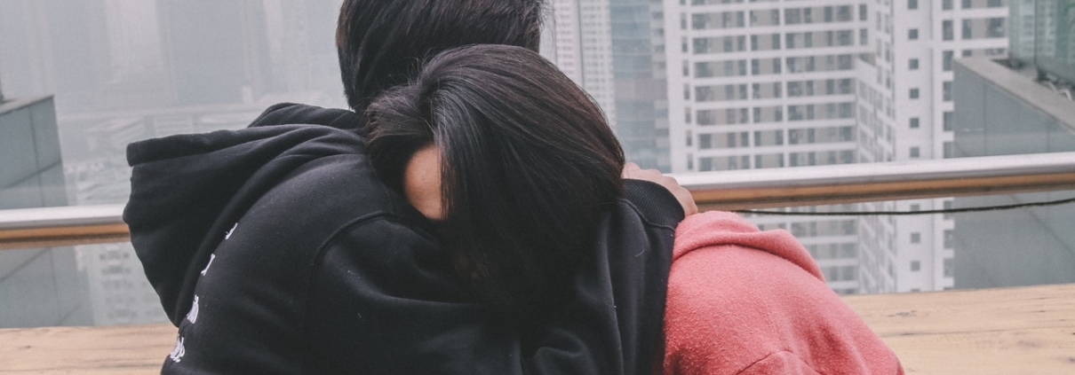 young woman being hugged by young man