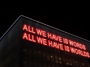 """neon lights that say """"all we have is words, all we have is worlds"""""""