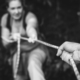 Blurred image of a hand holding a rope to support a woman climbing up