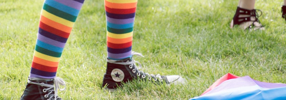 legs wearing rainbow socks and black Converse sneakers