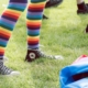 legs wearing rainbow socks and black Converse sneakers