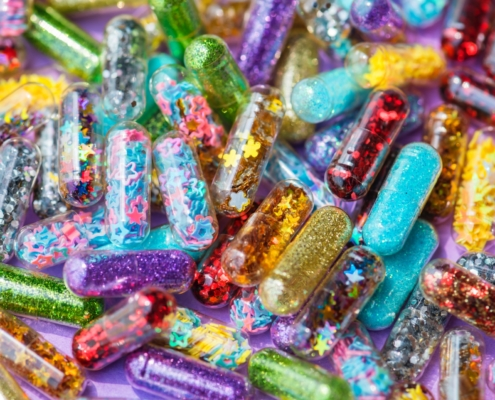 capsules filled with rainbow colours, glitter, and stars