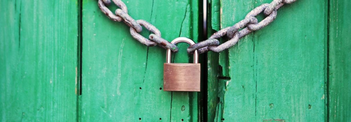 Padlock and chain on green door