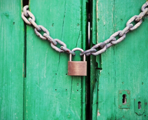 Padlock and chain on green door