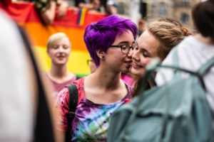 woman wearing tie die shirt kissing another woman