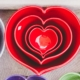 red heart-shaped ceramic bowls of different sizes stacked one inside the other