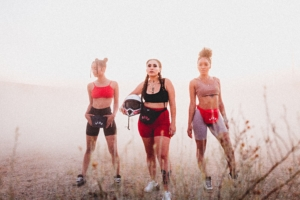 three fashionable and diverse women wearing gym clothes outdoors