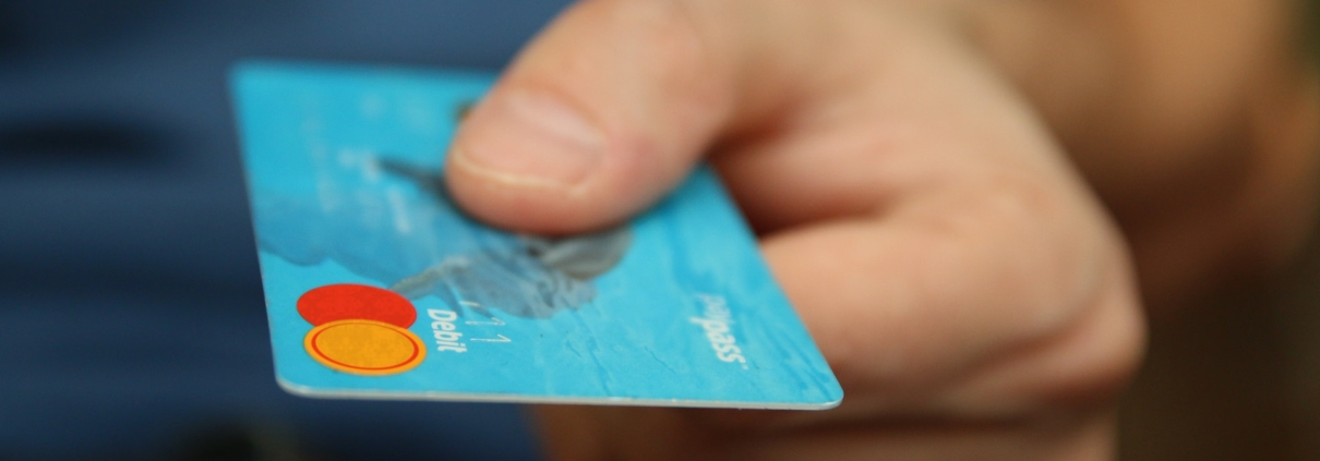 Hand holding a blue credit card