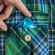 Hand putting a condom in the pocket of a blue and green checked shirt