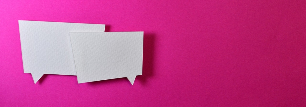 Two blank white text bubbles on a bright pink wall