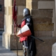 Knight in armour standing guard at a building
