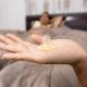 Condom sitting on top of a hand with background image showing a man under a bed sheet