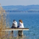 Man and woman sitting on a jetty over a lake and talking