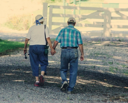 Elderly man and woman walking and holding hands