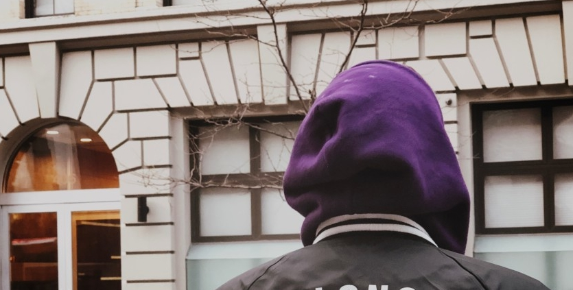 person in hoodie outside building